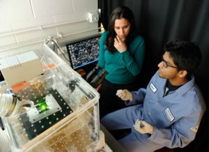 Assistant Prof. Rebecca Schulman, left, and postdoctoral fellow Abdul Mohammed used this single-molecule fluorescence microscope to track the nanotube bridge formation process. Photo by Will Kirk/Johns Hopkins University.